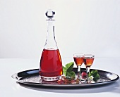 Wild strawberry liqueur in carafe and glasses on tray