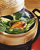 Trout in banana leaf in bamboo steamer