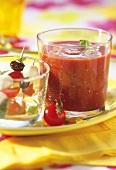 Glass of tomato juice, mozzarella & tomatoes on cocktail sticks