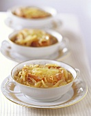 Three bowls of onion soup in a row