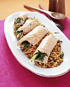 Salmon roulades with spinach filling on lentil salad