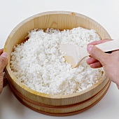Making sushi rice (stirring with a wooden spoon)
