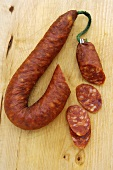Chorizo on wooden background, pieces cut off