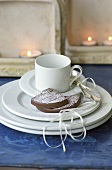 Pieces of chocolate cake with icing sugar beside coffee cup