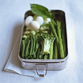 Green asparagus, beans, cress and quails' eggs in lunchbox