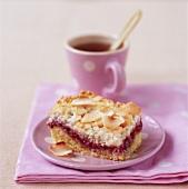 Piece of coconut raspberry cake with tea