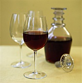 Red wine in glass and carafe beside empty wine glasses