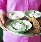 Woman serving goat's cheese dip with chives and bread