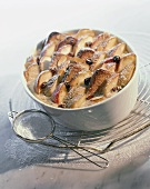 'Log pyre' (bread pudding) with apples, raisins & icing sugar