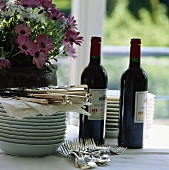 Pile of plates, cutlery, red wine and flowers on table