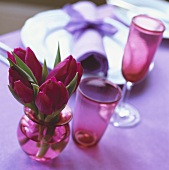 Red tulips in small vase beside place-setting