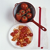 Cooked cherry tomatoes on plate, fresh tomatoes in strainer