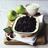 Blackberries in a dish, two green apples & rolled oats