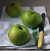 Three Granny Smith apples on tea towel with knife