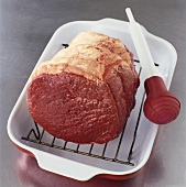 Raw rolled beef joint in roasting dish