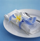 Place-setting with white fabric napkin, flower & blue bow