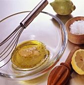 Vinaigrette in glass bowl with mustard, lemon and salt
