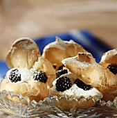 Cream puffs with cream and blackberries