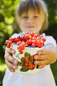 Child holding cup of redcurrants in the open air