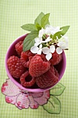 Raspberries, leaves and flowers in pink beaker