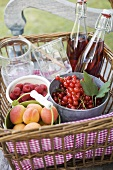 Berries, apricots, bottles of juice and jars in basket
