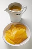 Orange segments in white bowl, orange juice in measuring jug