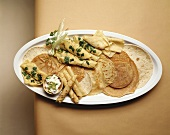 Various types of pancakes on white platter (overhead view)