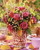 Vase of roses and autumn leaves