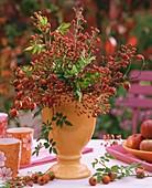 Autumnal arrangement of rose hips in orange vase