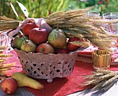 Autumn table decoration: pears, apples & cereal ears in basket