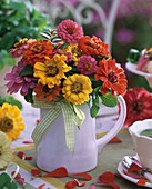 Yellow and red zinnias in jug (summery)