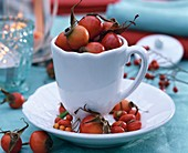 Autumnal table decoration: rose hips in coffee cups