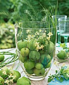 Green apples, asparagus fern & wild clematis in large glass vase