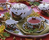 Fruit tea in teacup with robin motif, acorns, leaves