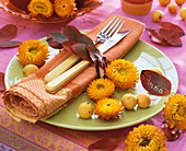 Autumnal place-setting with strawflowers and leaves