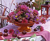 Asters, rose hips and chestnuts on glass pedestal stand