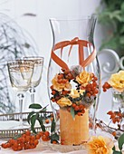Wind light with orange candle and flower wreath