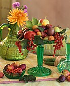 Apples, plums, mirabelles, redcurrants on glass stand