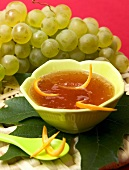 Grape jelly in bowl in front of fresh green grapes
