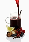 Pouring mulled wine into glass, ingredients in foreground