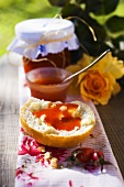 Rose hip jam on bread roll & jar of jam on table in the open air
