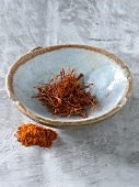 Saffron threads in bowl, saffron powder beside it