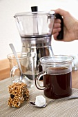 Coffee in glass mug, sugar cube, muesli bar, coffee maker
