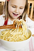 Girl lifting spaghetti out of bowl with spaghetti server