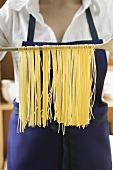Hanging home-made pasta over wooden spoon to dry