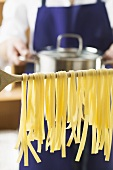 Home-made ribbon pasta on wooden spoon