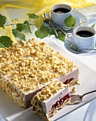 Cherry cream cake with rum and crumble, two cups of coffee