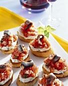 Crostini with tomatoes, soft cheese and anchovy fillets