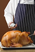 Chef checking roast turkey with meat thermometer