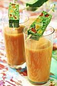 Two glasses of gazpacho, vegetable terrine on cocktail sticks